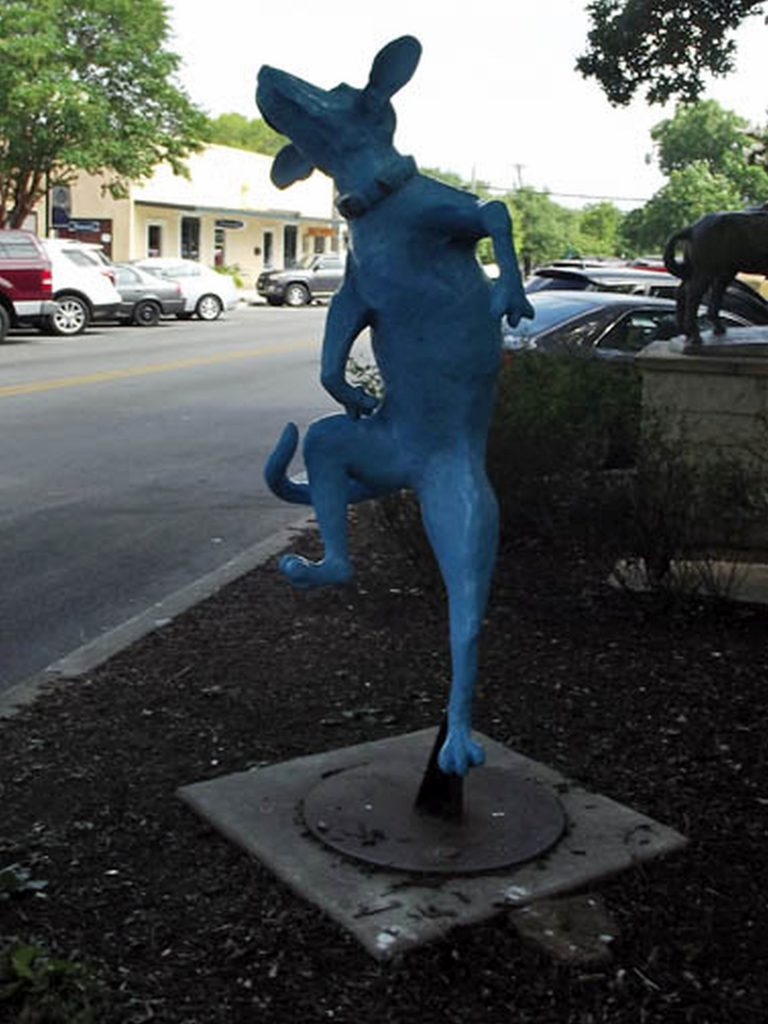 Artwork of a whimsical statue of a dancing dog near the Visitor's Center on the Square.